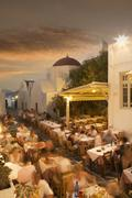 Time lapse view of tourists eating in sidewalk cafe at sunset, Mykonos, - stock photo