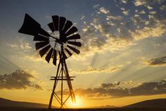 Silhouette of windmill under dramatic sunset sky Stock Photos