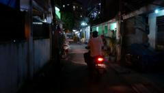 Walk on dark night alley in slum, narrow way, motorbike overtake and run ahead - stock footage