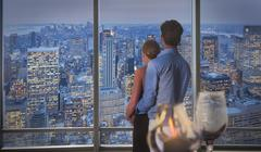 Caucasian couple admiring New York cityscape from window, New York, United Stock Photos