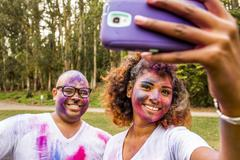 Couple taking selfie covered in pigment powder Stock Photos