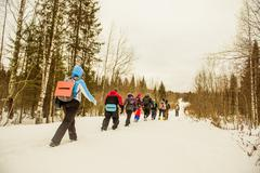 Caucasian hikers walking in a row on snowy path Stock Photos