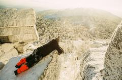 Caucasian hiker laying on snowy rock formations Stock Photos