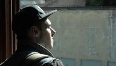 A young man in a cap looks out the window . squinting in the sun . Poplar fluff. Stock Footage