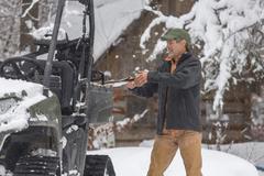 Mixed race man standing near snow vehicle Stock Photos