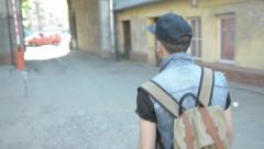 a young man in a cap goes in the direction arch - stock footage