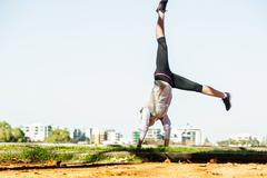 Young fit woman doing simple acrobatics exercise routine in autumn park with - stock photo