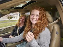 Caucasian teenage girl showing key with mother in car Stock Photos