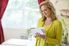 Caucasian woman sorting mail in living room Stock Photos