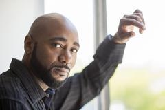 Black man standing at window Stock Photos