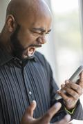 Frustrated black man using cell phone near window Stock Photos