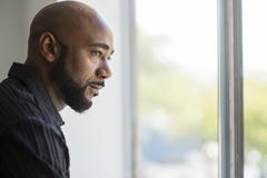 Black man looking out window Stock Photos