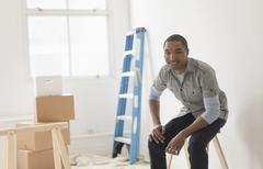 Black man sitting in room under renovation Stock Photos