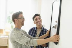 Caucasian gay couple hanging picture on wall Kuvituskuvat