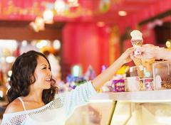 Chinese woman buying ice cream cone in shop - stock photo