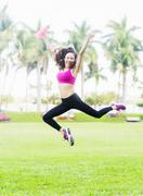 Chinese woman jumping for joy in park Stock Photos