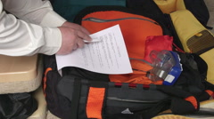 Traveler packing travel bag using checklist of items to pack for summer vacation Stock Footage