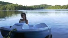 Woman talks while  in pedal boat Stock Footage