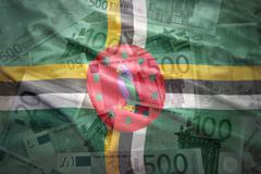colorful waving dominica flag on a euro money background - stock photo