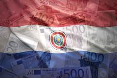 Stock Photo of colorful waving paraguayan flag on a euro money background