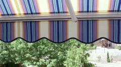 Terrace of hotel with retractable striped awning overlooking seaside Stock Footage