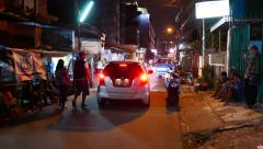 Car slow drive away on night slum street, camera start and move behind Stock Footage