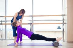 Aerobics Pilates personal trainer helping women group in a gym c Stock Photos
