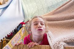 Caucasian girl playing in blanket fort Stock Photos