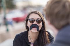 Teenage girl wearing fake mustache Stock Photos