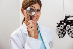 Doctor looking through magnifying glass - stock photo