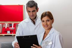 Happy ophthalmologists looking at chart Stock Photos