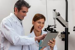 Happy ophthalmologists looking at tablet Stock Photos