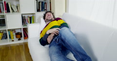 Man feeling stomach sick at home on couch Stock Footage