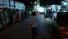 Woman throw out trash to container, night street, parallax shot Stock Footage