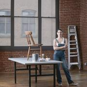 Mixed race woman painting chair in loft Stock Photos