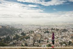 Caucasian woman admiring scenic view of cityscape, Granada, Spain Stock Photos