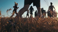 Group of people running on a field in sunset, slow motion - stock footage