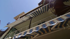 Front of the hotel with retractable striped awnings and spiral staircase Stock Footage