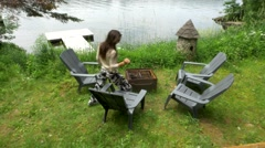 Woman sits in chair near fire pit at cottage Stock Footage