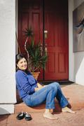 Barefoot woman sitting on front stoop Stock Photos