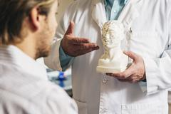 Caucasian acupuncturist showing patient carved bust with diagram Stock Photos