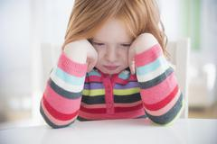 Caucasian girl crying at table - stock photo
