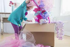 Caucasian girl unpacking dress-up clothes from box Stock Photos
