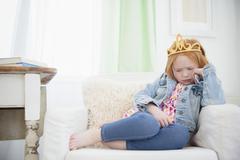 Upset Caucasian girl pouting in armchair Stock Photos
