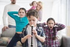 Caucasian family covering ears with boy playing recorder Stock Photos