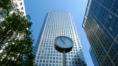 People rushing around a clock in front of One Canada Square in Canary Wharf Stock Footage