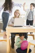 Caucasian mother using laptop with chaotic children - stock photo