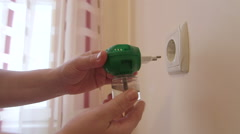 Woman plugs electric liquid mosquito repeller into the outlet close-up Stock Footage