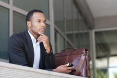 Black businessman thinking outside building - stock photo