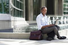 Black businessman using laptop near urban fountain - stock photo